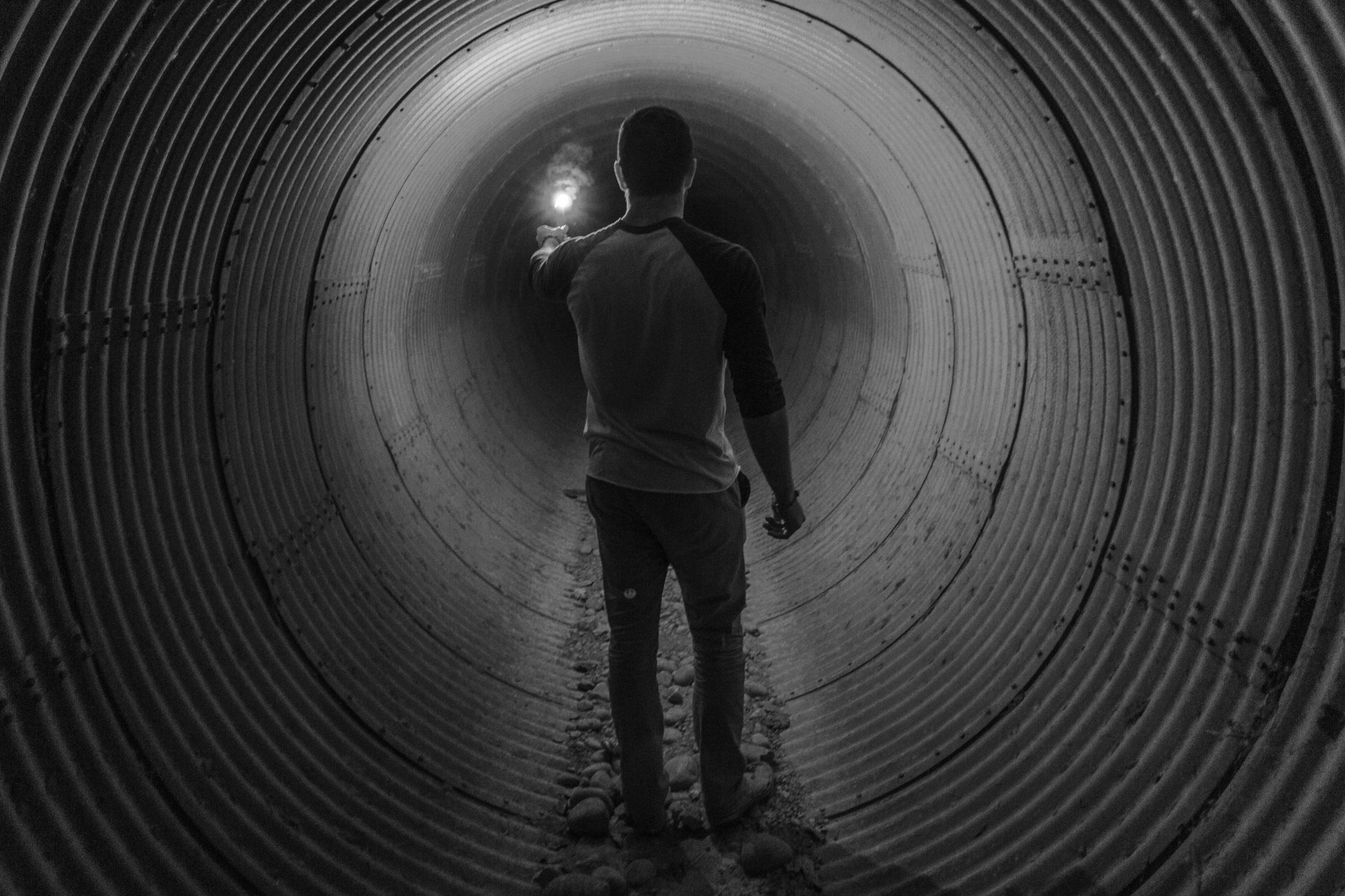 black and white photo pf man walking in huge pipe, holding a light